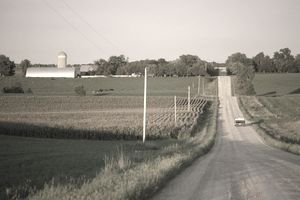 Truck on a farmland road at sunset with barn silo to the left