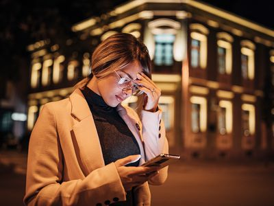 A woman rubs her head while looking at her phone.