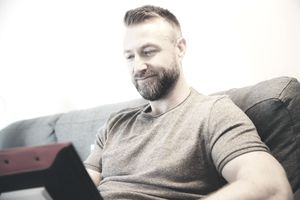 bearded man reading from laptop on couch