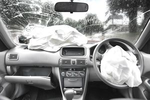 car after an accident with airbags deployed and broken windshield