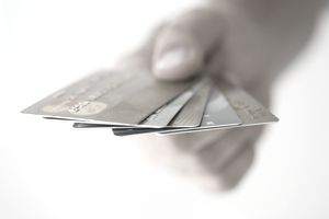 five credit and debit cards fanned out in a person's hand
