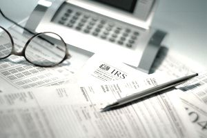Calculator, pen and IRS tax forms including Form 1099-C