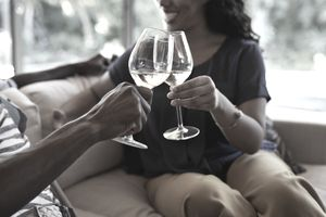 Couple at home toasting their paid-off mortgage with wine