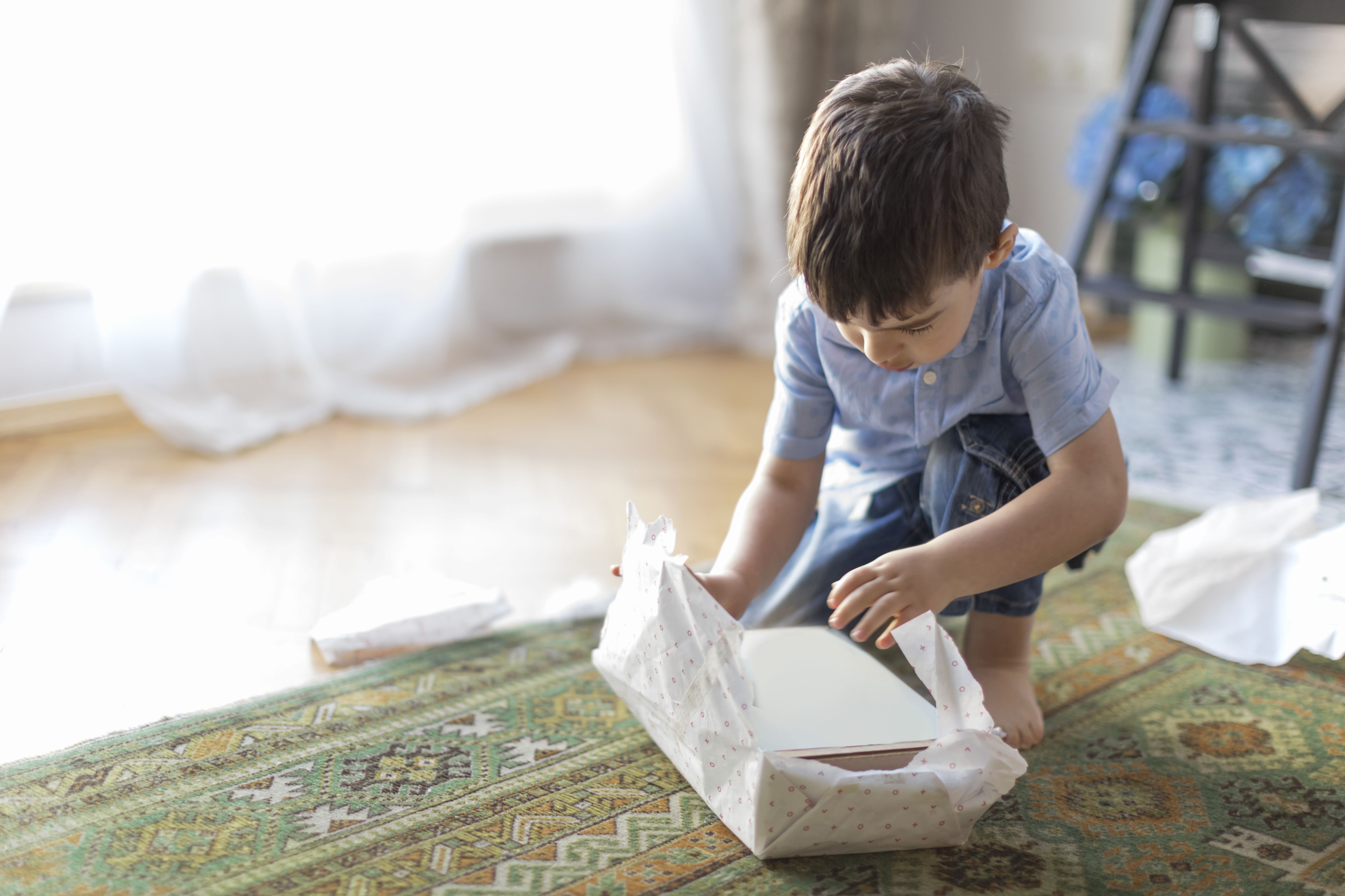 Young male child unwrapping a gift