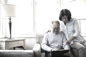 Senior couple at home using tablet