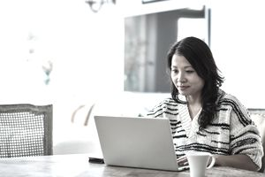 Woman using laptop and sitting at desk at home.