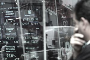 Passersby watch as the stock numbers are posted at the close of the market on the Nasdaq building in Times Square.