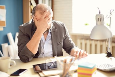 A man seated at his home office clutches his forehead in frustration.