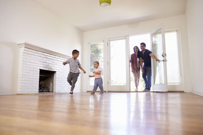 two kids running into an empty house. two adults are behind them, coming through the door.