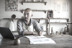 A shop owner doing his monthly financial planning and bookkeeping at a desk with laptop