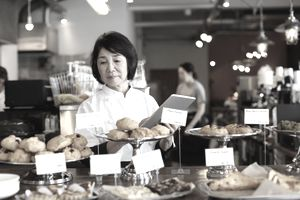 An older woman working at bakery checking inventory with a handheld device.