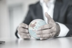 Close-up of the hands of a foreign investor holding a globe.