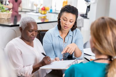Mid adult woman helps her senior mother with medical paperwork.
