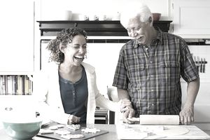 An older man and a laughing middle-aged woman stand behind a counter in a kitchen.