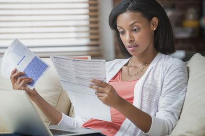 Woman sitting on couch reviewing her insurance policy and grace period