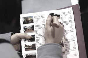 woman taking notes on listing of homes for sale
