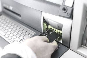 Person putting debit card into an ATM machine card reader
