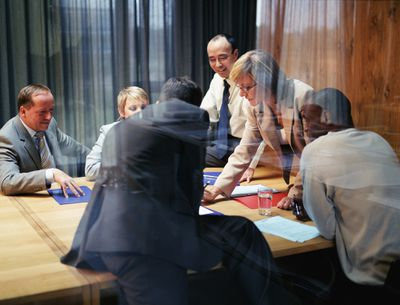 A group of company leaders meet in a conference room