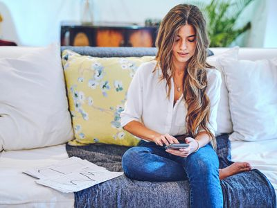 A young woman sits on a couch and uses a smartphone.