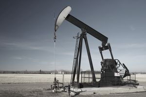 An oil derrick drills for crude oil in a field