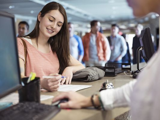 A smiling young woman prepares to sign a student loan forbearance or deferment loan form at a bank desk while other students line up behind her.