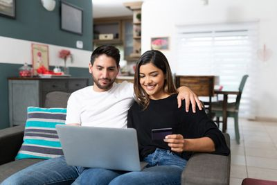 Couple shopping on laptop sitting on sofa in living room at home