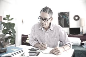 A man sitting at a desk with a calculator is writing down information about.