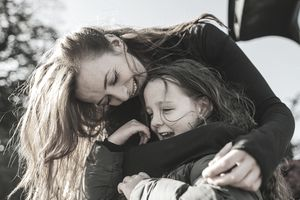 Mother bends down to hug young daughter from behind