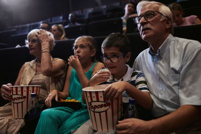 As cinemas reopen, grandparents and their grandchildren watch a movie.