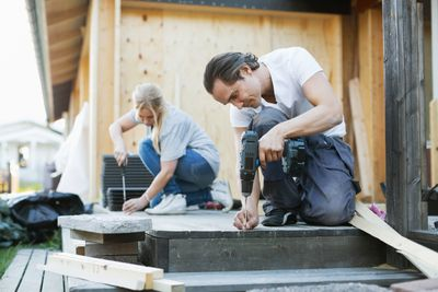 Couple working outside house during home improvement