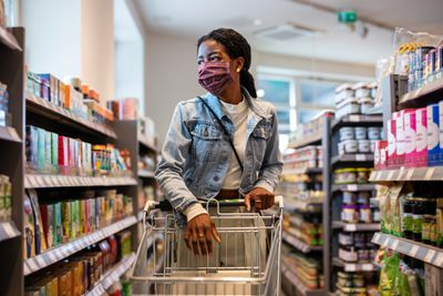 African woman wearing protective face mask buying grocery at a supermarket. Female customer shopping at a local grocery store.