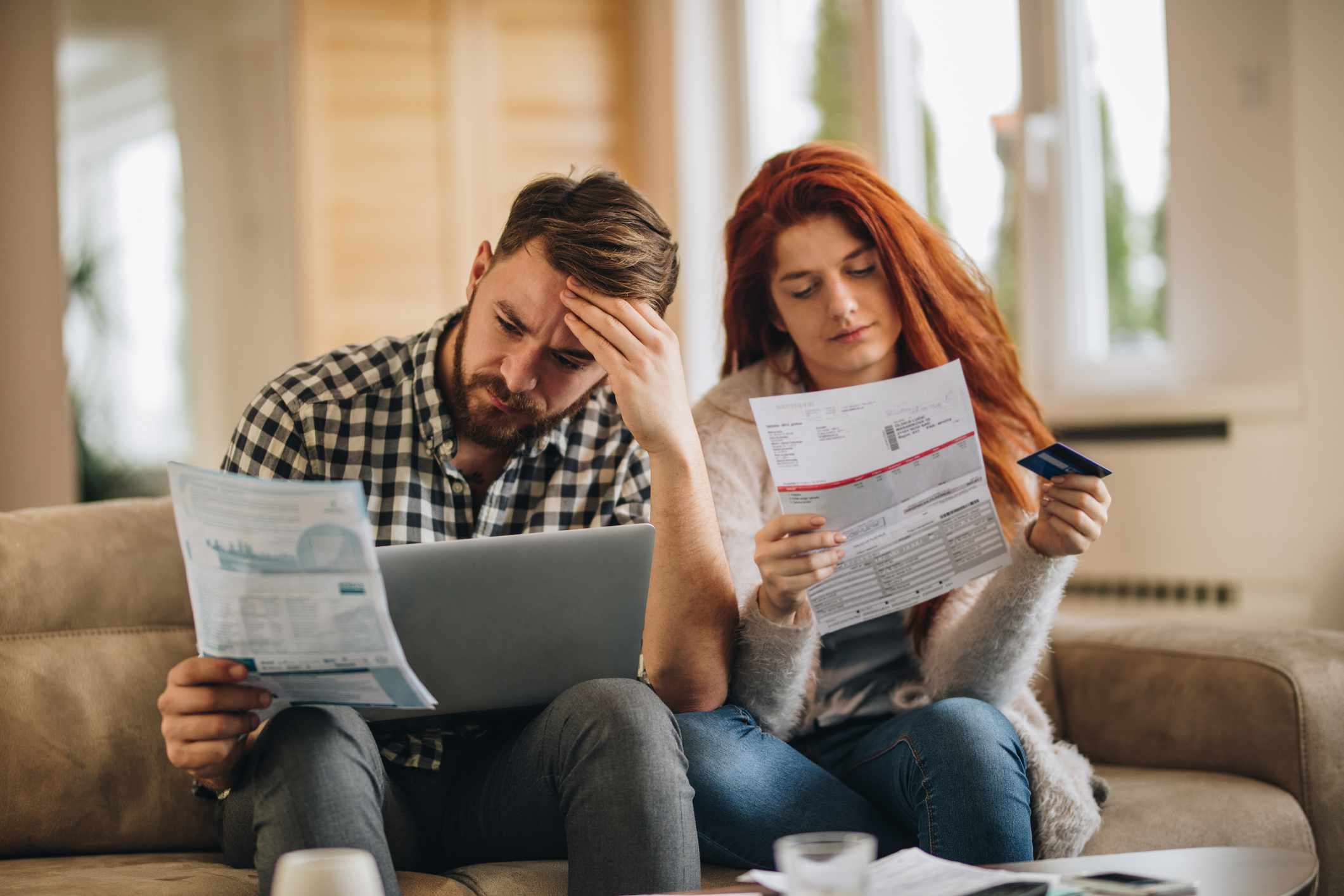 Couple looking distressed as they review credit card bills