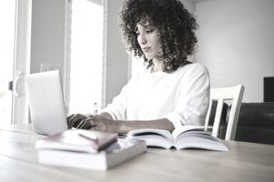 Female returning college student uses a laptop at a kitchen table with textbooks nearby