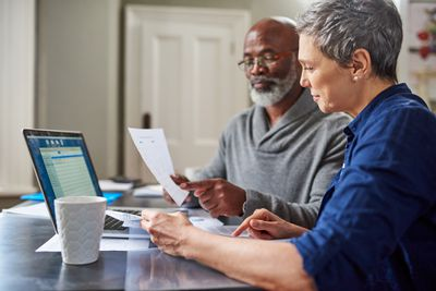 Senior couple at computer looking over retirement paperwork