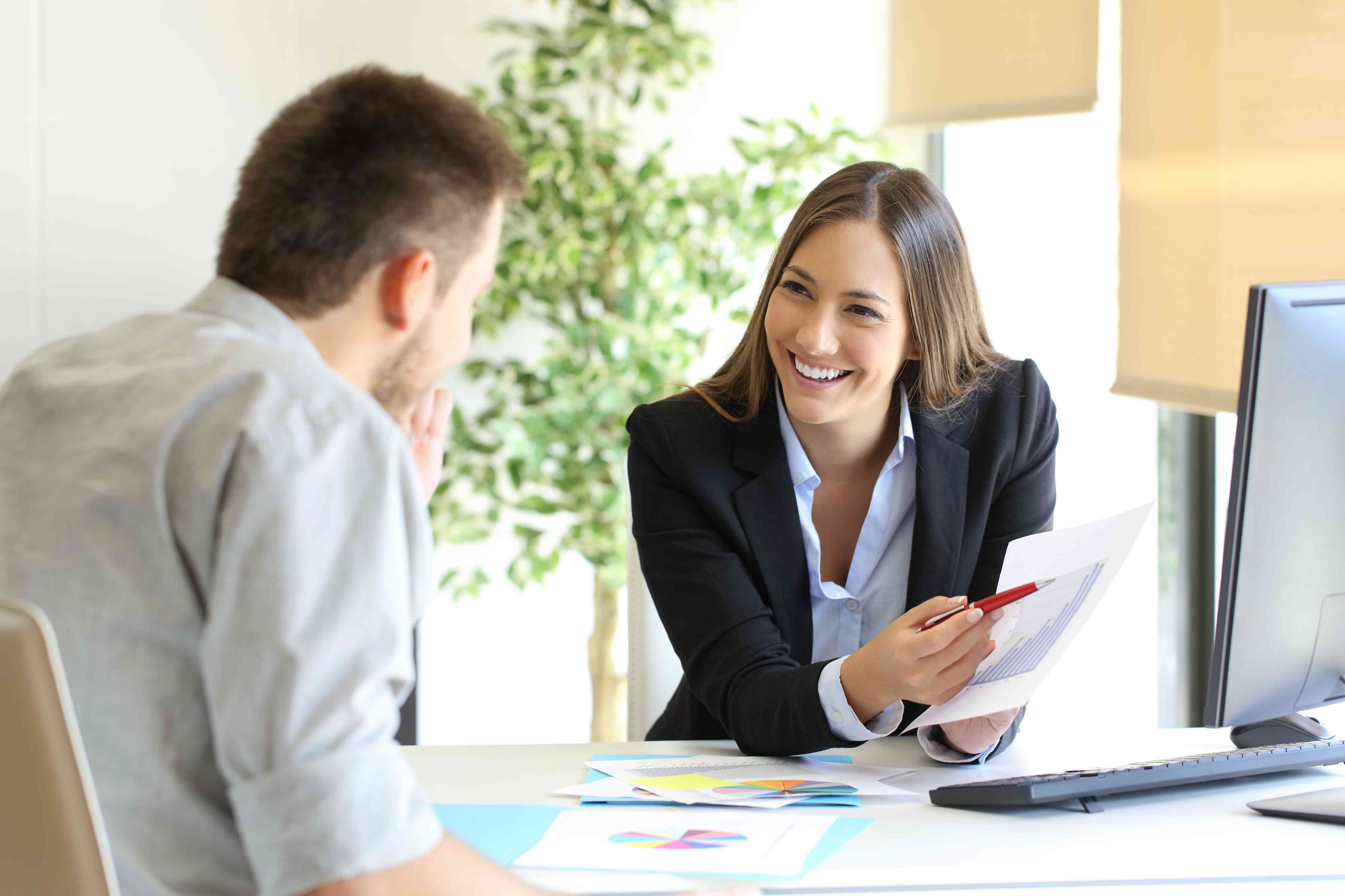 Smiling woman in HR with computer and paper telling male employee that their employer plan allows Roth contributions