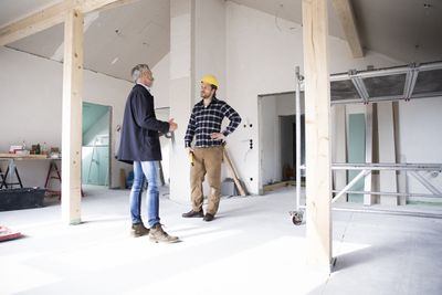 Architect and construction worker talking while standing in a building under renovation