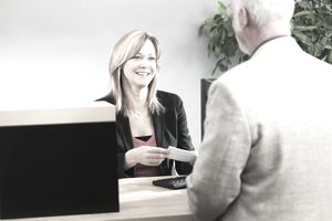Bank Teller Serving Customer Over Retail Banking Service Counter
