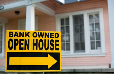 """""""Bank-owned open house"""" sign in front of a home"""