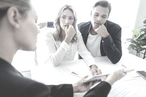 A couple appear worried as they speak with a professional and review documents.