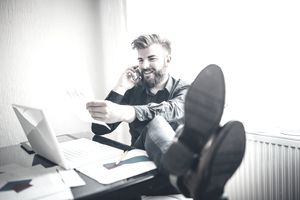 Relaxed man talking on cellphone in an office with his feet on the desk
