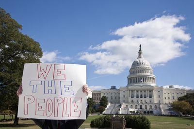 A person holding a placard in front of the US Capitol Building