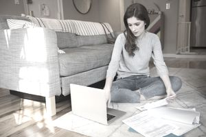 Caucasian woman sitting on floor paying bills with laptop