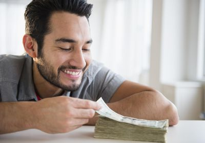 A man grins as a large stack of currency laying on a table