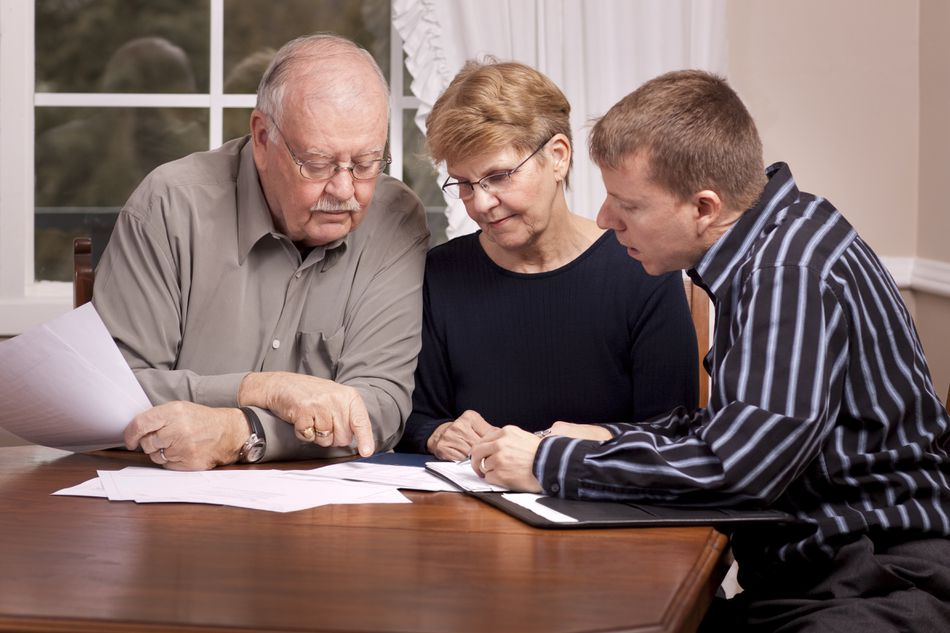 Financial advisor with senior couple going over paperwork