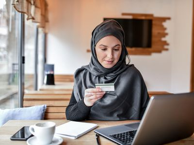 A woman with a laptop holds a credit card.