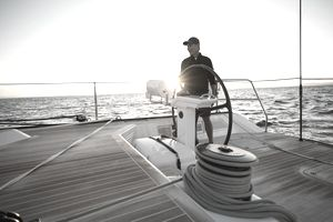 A man stands at the wheel of a large and luxurious sailing yacht with the sun setting behind him.