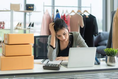 Small business owner with laptop and calculator frustrated by paperwork