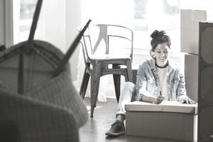 Young woman with moving boxes and furniture