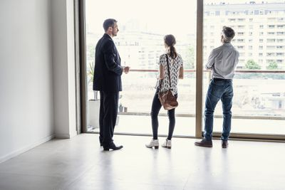 real estate agent showing a house to a man and woman