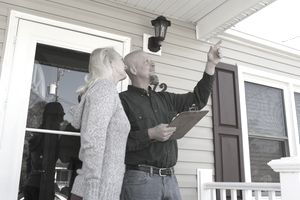 Home inspector pointing out a problem to a home owner while standing on a front porch.